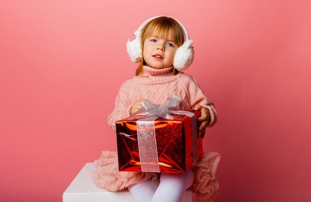 Счастливая маленькая улыбающаяся девочка в зимних наушниках с рождественской подарочной коробкой.