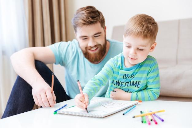 幸せな幼い息子とお父さんが座って、テーブルにカラフルなマーカーで描いています