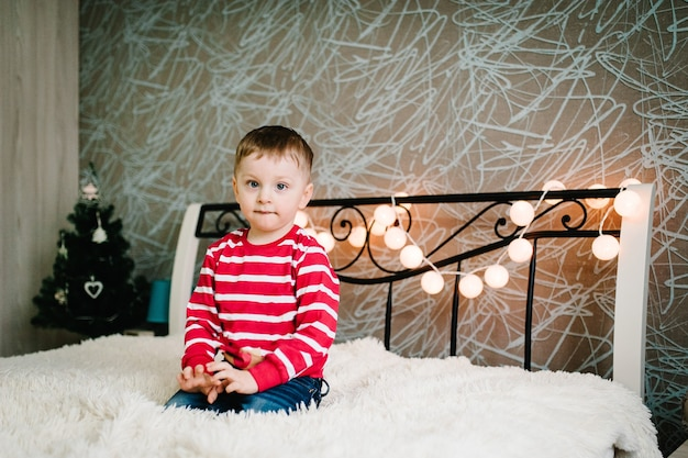 Счастливый маленький сын в свитерах санта-клауса, играет и сидит на кровати.