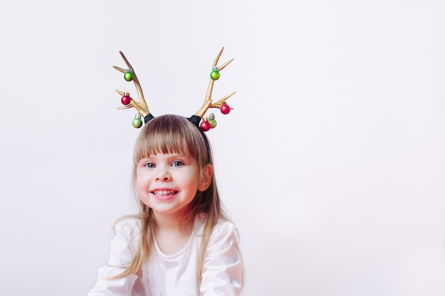 Happy little toddler 3-years old girl with christmas deer horn headband on white background with blank space for text