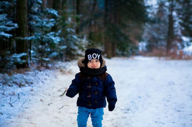 Счастливый маленький мальчик-малыш удивляется снежинкам в зимнем лесу