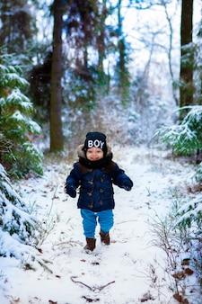 冬の森の雪の薄片を不思議に思っている幸せな小さな幼児の男の子