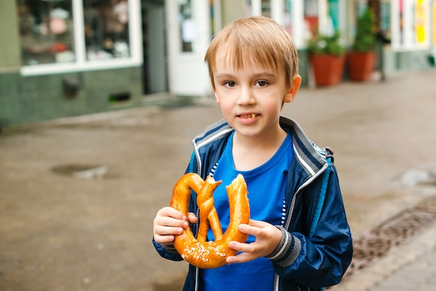 Happy little tourist eating pretzel outdoors. family vacation, travel and lifestyle.
