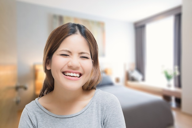 Happy living concept with smiling asian woman with interior blurred background
