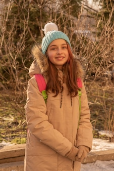 Счастливая одинокая привлекательная молодая девушка в теплой одежде с рюкзаком, стоящим в зимнем лесу или парке.