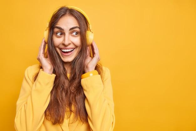 행복한 장발의 매력적인 여성은 즐겁게 스테레오 헤드폰에 손을 얹고 웃는다