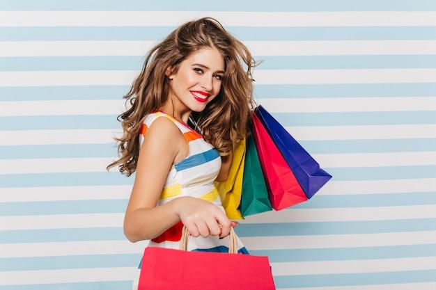 Счастливая длинноволосая женщина улыбается после покупок. портрет довольной белой девушки с бумажными пакетами.