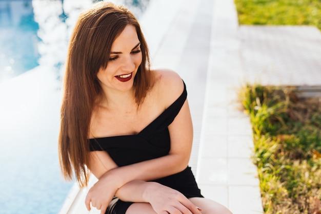 검은 드레스를 입은 행복한 장발 젊은 여성이 푸른 수영장 옆에 앉아 태양 아래 웃고 있다