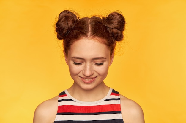 Happy looking, charming red hair woman with two buns. wearing striped shirt and watching down with smile, shy