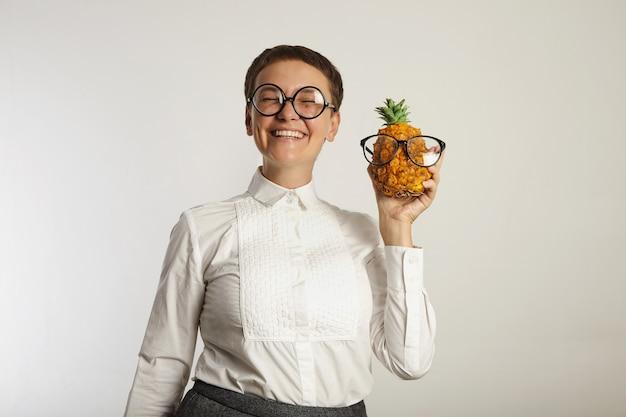 Insegnante pazzo sembrante felice con un ananas in vetri di corrispondenza isolati su bianco