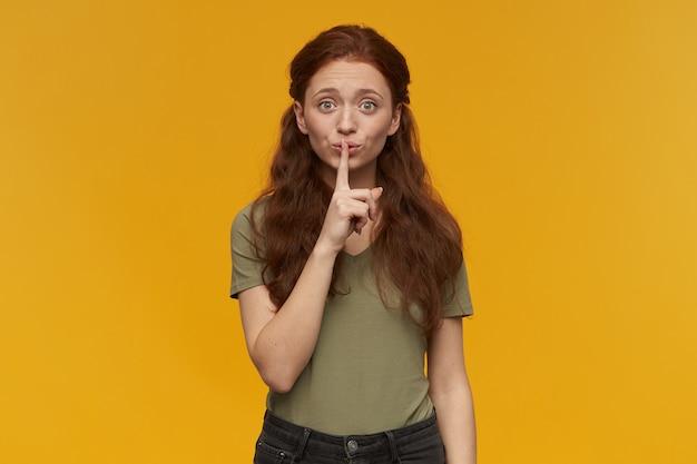 幸せそうな女の子、長い髪の魅力的な赤毛の女性。緑のtシャツを着ています。感情の概念。沈黙のサインを見せて、静かにするように頼みなさい。オレンジ色の壁に隔離