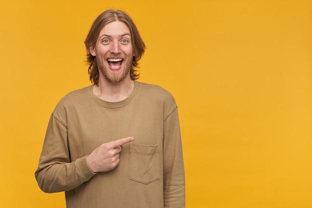 幸せそうな男性、金髪の髪型の陽気なひげを生やした男。ベージュのセーターを着ています。黄色い壁の上に隔離されたコピースペースで右に人差し指