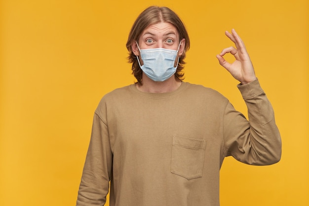Счастливый смотрящий мужчина, позитивный бородатый парень со светлой прической. в бежевом свитере и медицинской защитной маске. показываю хорошо знаком. изолированные над желтой стеной
