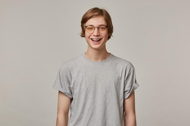 행복 찾는 사람, 금발 머리를 가진 잘 생긴 남자. 회색 티셔츠, 안경을 착용하고 교정기가 있습니다. 사람과 감정 개념. 보고 넓게 웃고 회색 벽 위에 절연