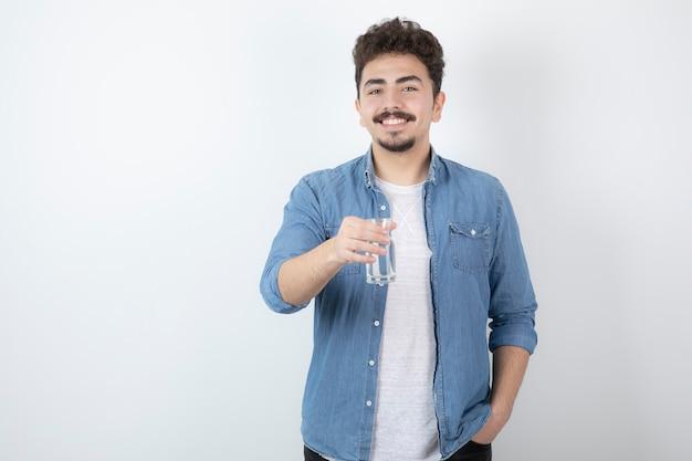 白で水のガラスを保持している幸せそうな男。