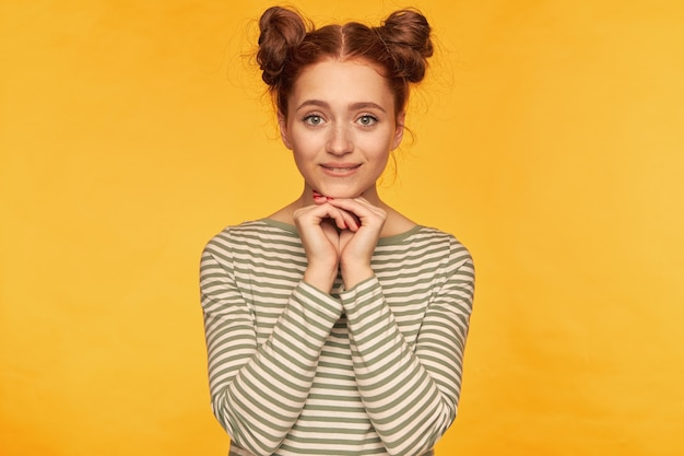Happy looking red hair woman with two buns. holding hands folded under her chin, in anticipation. wearing striped sweater