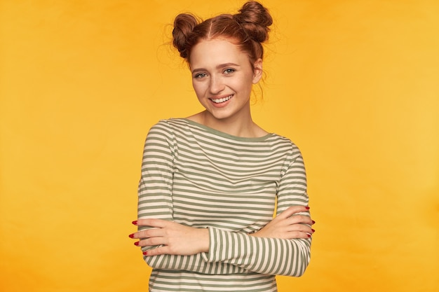 Happy looking red hair woman with two buns. wearing striped sweater and holds hands crossed on a chest