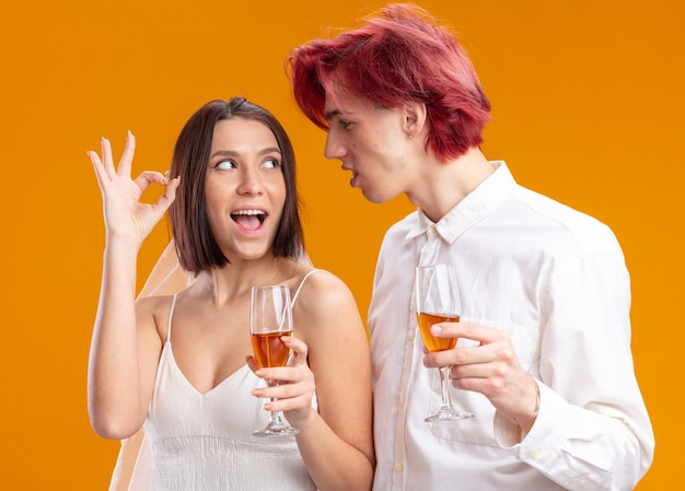행복 한 찾고 웨딩 커플 신랑과 웨딩 드레스에 신부 확인 표시를 보여주는 샴페인 신부를 마시는 함께 쾌활 한 포즈 미소
