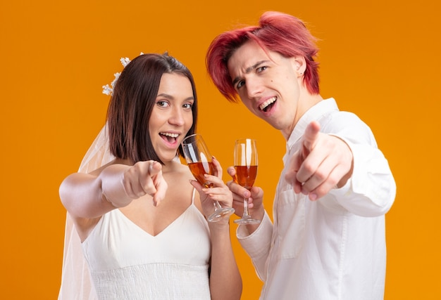 人差し指を前に向けてシャンパングラスを持って元気にポーズをとって笑顔のウェディングドレスを着た幸せそうな結婚式のカップルの新郎と新婦