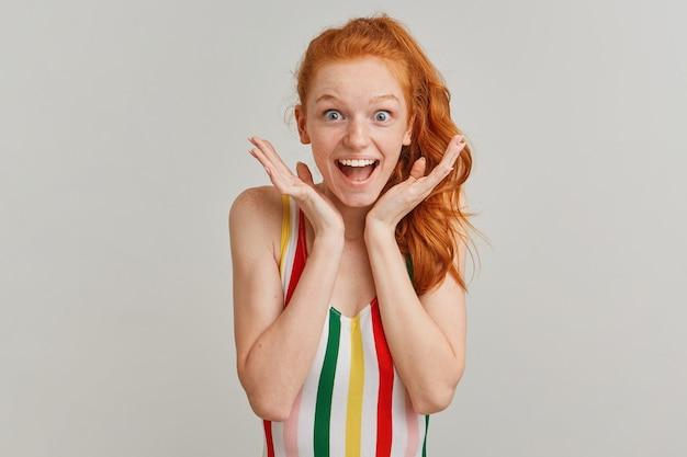 Счастливая женщина, позитивная рыжая девушка с конским хвостом и веснушками, в полосатом красочном купальнике