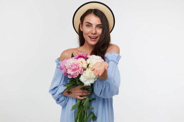 Happy looking woman with brunette long hair. wearing a hat and blue dress. holding a bouquet of flowers and showing open palm