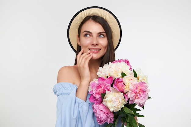 Happy looking woman with brunette long hair. wearing a hat and blue dress. holding bouquet of flowers and touching her chin