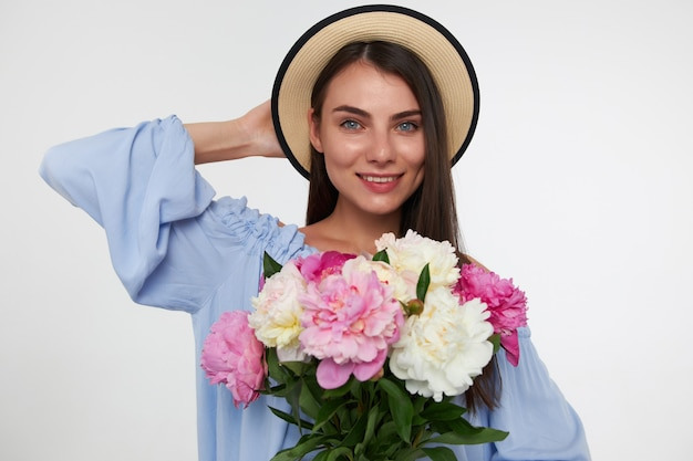 Happy looking woman with brunette long hair. wearing a hat and blue dress. holding bouquet of flowers and touching her head