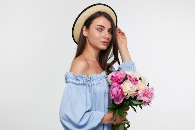 Happy looking woman with brunette long hair. wearing a hat and blue pretty dress. holding a bouquet of flowers, touching hair