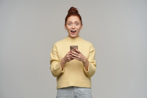Счастливая смотрящая женщина с рыжими волосами, собранными в пучок. в пастельно-желтом свитере и джинсах. держите смартфон. удивлен сообщением. изолированные над серой стеной