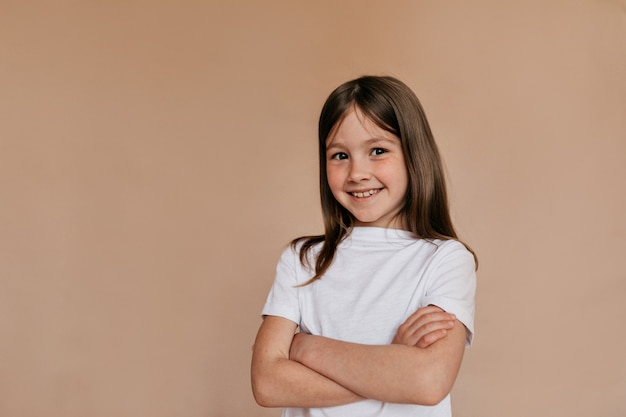 Счастливая привлекательная девушка в белой футболке позирует над бежевой стеной.