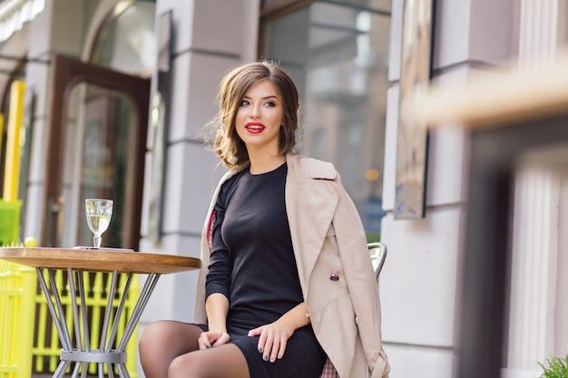 黒のドレスとベージュのコートを着た幸せな愛らしい女性が屋外のカフェテリアに座って、グラスワインで休んでいます