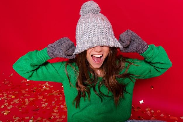 Счастливая милая женщина в зеленом свитере позирует над красной стеной, натягивает зимнюю шапку на глаза и улыбается
