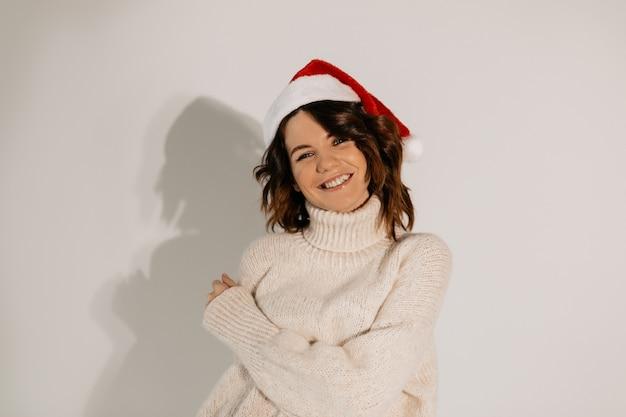 Счастливая милая женщина с волнистыми волосами в шляпе санта-клауса и белом вязаном свитере позирует