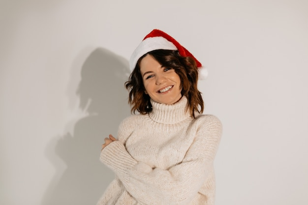 Happy lovable woman with wavy hair wearing santa hat and white knitted sweater posing