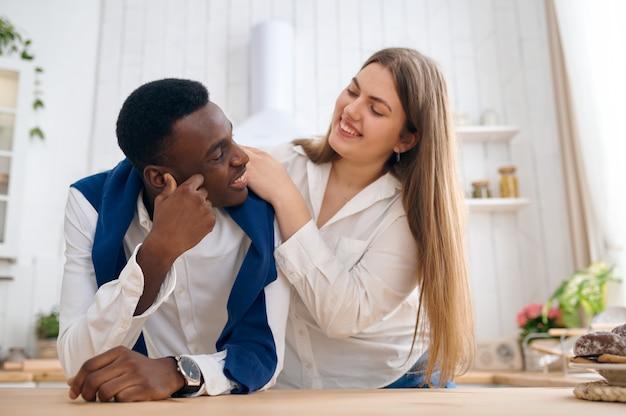 행복한 사랑의 커플, 부엌 카운터에서 아침 식사. 쾌활한 남자와 여자는 아침에 여가를 보냅니다. 돌보는 아내가 남편을 먹인다
