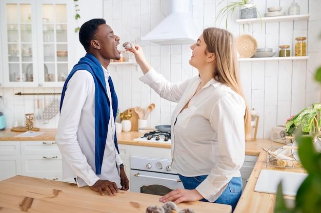 幸せな愛のカップルがキッチンで朝食を調理します。朝は元気な男女のレジャー。思いやりのある妻が夫を養う