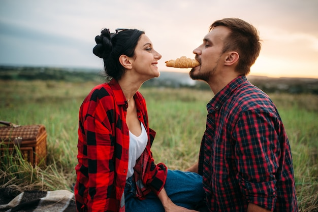 Happy love couple eating croissants on picnic in summer field. romantic junket of man and woman