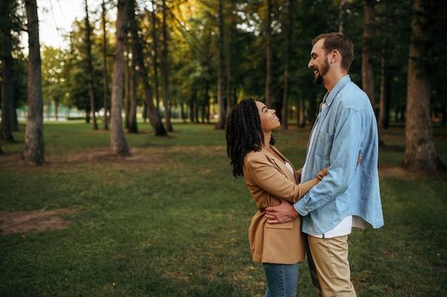 Счастливая влюбленная пара обнимая, романтическая прогулка в парке. мужчина и женщина отдыхают на открытом воздухе, зеленая лужайка. семейный отдых на лугу летом