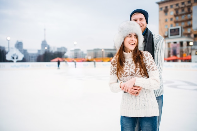Happy love couple hugs on skating rink. winter ice-skating on open air, active leisure, man and woman skates together