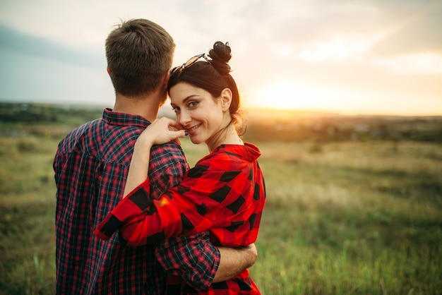 Happy love couple hugs in summer field at sunset. romantic junket of man and woman, picnic on the meadow