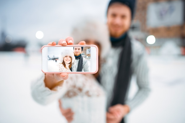 Happy love couple makes selfie on skating rink. winter ice-skating on open air, active leisure, man and woman skates together