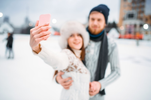 Happy love couple makes selfie on skating rink