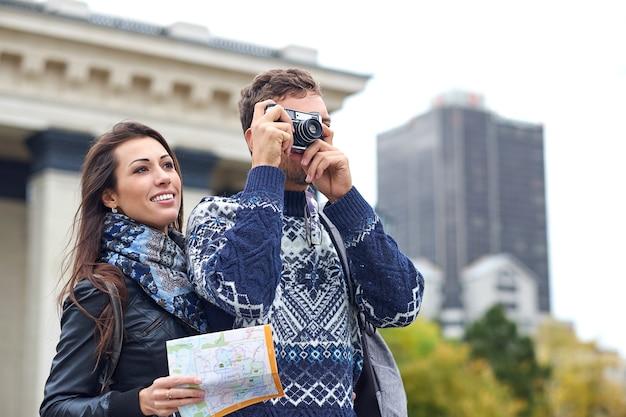 遠足や市内観光で写真を撮る観光客の幸せな愛のカップル。地図とレトロなカメラと一緒に旅行