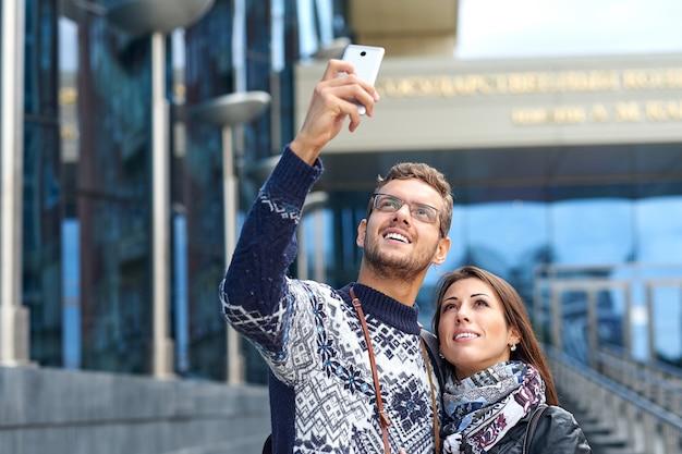 Счастливая влюбленная пара туристов, делающих фото на экскурсии или экскурсии по городу. путешествуем вместе