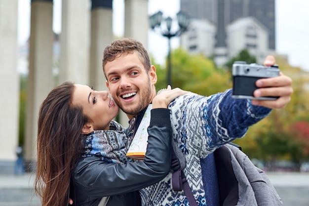 都市のレトロなカメラで自分撮りをしている観光客の幸せな愛のカップル。写真で男性にキスする女性
