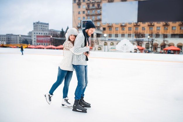 Happy love couple poses on skating rink. winter ice-skating on open air, active leisure, man and woman skates together