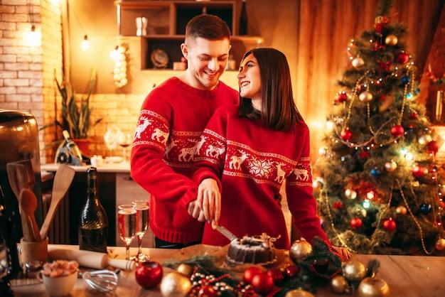 幸せな愛のカップルは、クリスマスケーキ、お祝い料理を味わいます。一緒にクリスマスのお祝い、若い家族の幸せ