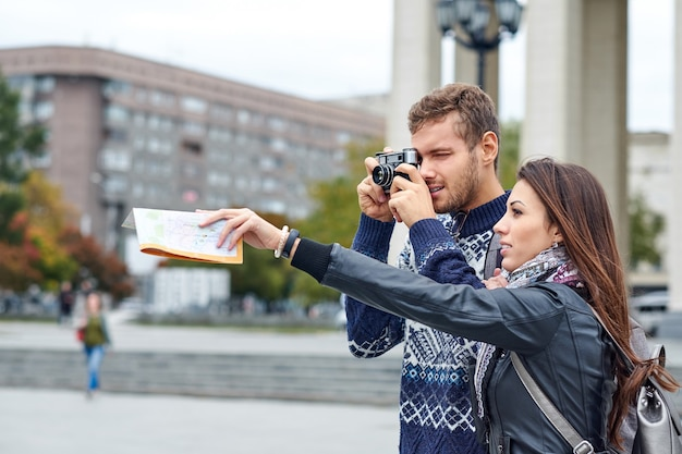 Happy love couple of tourists taking photo on excursion or city tour.