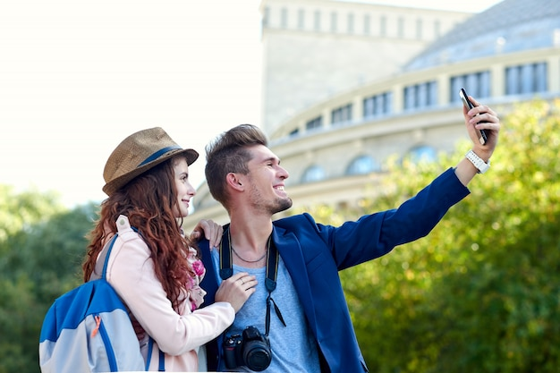 Happy love couple of tourists taking selfie in old city
