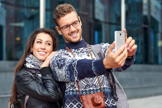 Happy love couple of tourists taking selfie in urban city